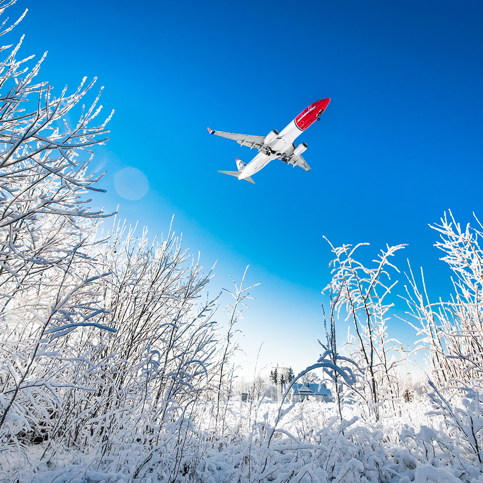 Norwegian plane flying over snow-covered field